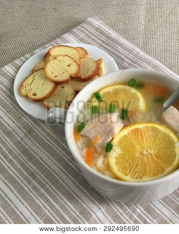 Delicious Chicken Soup With Lemon, Rise, Carrot, Green Onion And Bread Sticks Aside. Rustic Tableclo