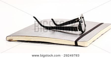 Glasses and notebook on the table