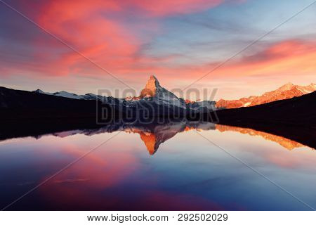 Splendid landscape with colorful sunrise on Stellisee lake. Snowy Matterhorn Cervino peak with reflection in clear water. Zermatt, Swiss Alps