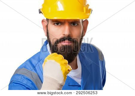 Close Up Portrait Of Bearded Angry Man Builder In Yellow Helmet And Blue Uniform Threatening With Fi