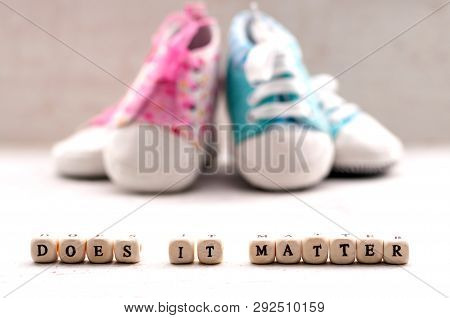 888126c2b8d6 Pink And Blue Baby Booties On A Light Background. Inscription Does It Matter