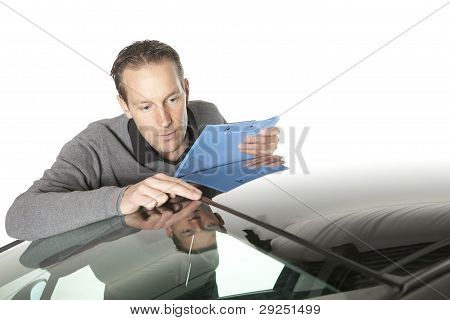 Male insurance agent looking at luxurious car over white background poster