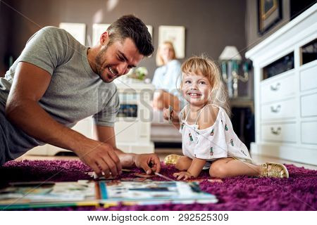 Smiling little girl playing with puzzles with her father
