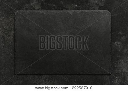 Black On Black. Empty Black Granite Stone Rectangle Board On Black Textured Cement Background, Top V