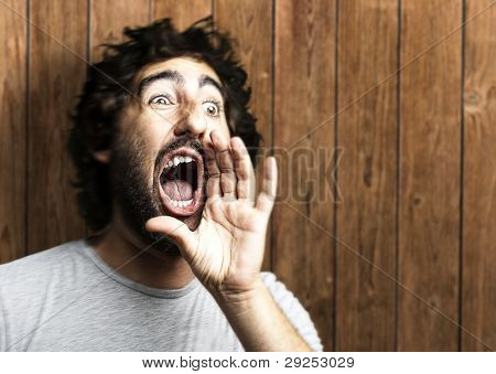 portrait of a young man shouting against a wooden wall