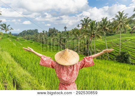 Relaxed Fashionable Caucasian Woman Wearing Red Asian Style Kimono And Traditional Asian Paddy Hat,