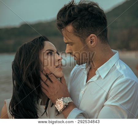 Attractive young couple on the beach at sunset