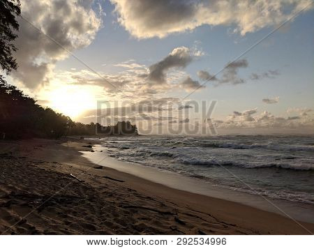 Beautiful Sunset Over The Ocean With Waves Moving To Shore On The North Shore Of Kauai, Hawaii