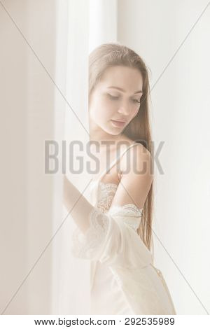 Attractive Young Seminude Girl In Night Clothes Posing Sexually By The Window