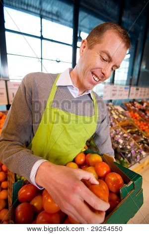 A happy grocery store owner looking over a box of ripe tomatoes