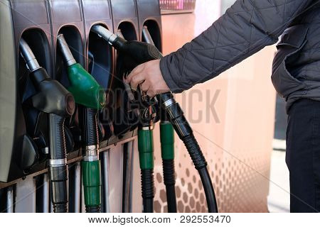 Man Fills Up His Car With A Gasoline At Gas Station. Petrol Station Pump. To Fill Car With Fuel. Gas