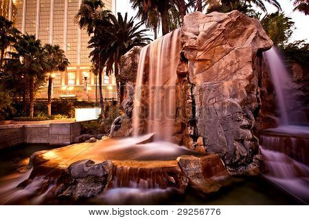 Artificial waterfall with palm trees