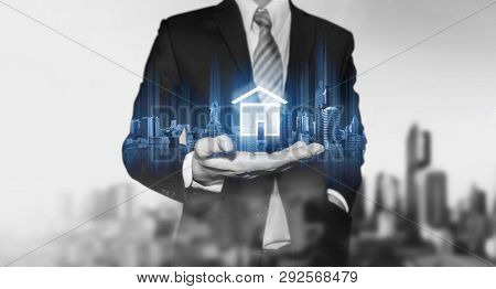 Businessman Holding Modern Buildings Hologram, And Home Icon. Real Estate Business, Building Technol