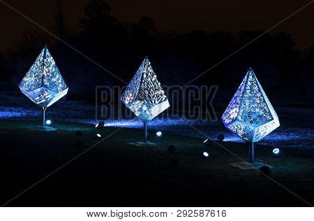 Three Holiday Fixtures Illuminated By Blue Colored Floodlights At Night In Park