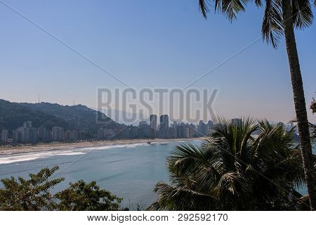 Sao Vicente, Brazil - July 2018:  Elevated Wide Shot View Through Palm Trees Showing Shoreline Of Th