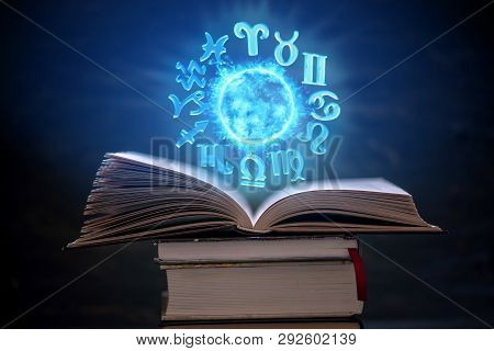 Open Book On Astrology On A Dark Background. The Glowing Magical Globe With Signs Of The Zodiac In T
