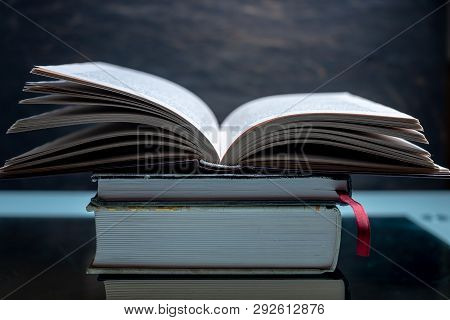 Open Book On A Stack Of Books On A Table On A Dark Background. Exam Preparation In Schools And Colle