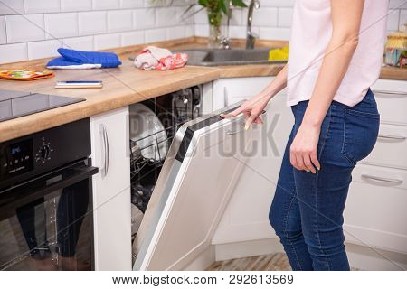 Washing Dishes In The Dishwasher. The Woman Puts Dirty Dishes In The Dishwasher. Opening And Closing
