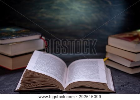 Open Book On A Stack Of Books On A Table On A Dark Background. Education And Reading Of Paper Books