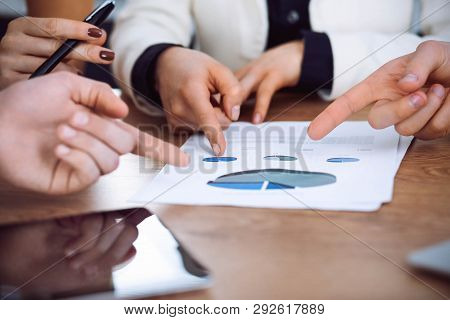 Group Of Businesspeople Or Lawyers Discussing Contract Papers And Financial Figures While Sitting At