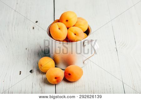 Mellow apricots in metal mug over light wooden surface poster