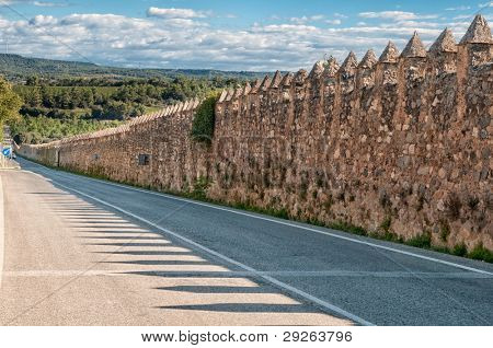 Medieval fortified wall near modern road, Monastery of Santa Maria de Poblet, Spain