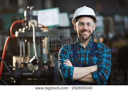 Waist Up Portrait Of Bearded Factory Worker Wearing Hardhat Looking At Camera While Standing In Work