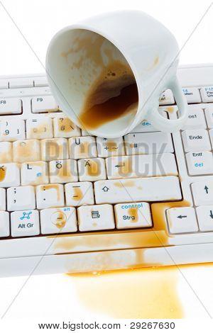 Tasse Kaffee verschüttet auf einer Computertastatur. Schadensversicherung.