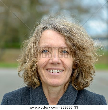 Smiling middle aged woman in grey coat with curly hair and wrinkled face frontal bust portrait outdoors, with trees blurred in background poster