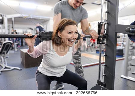 Middle-aged Woman Doing Sports Exercise In Fitness Center. Personal Gym Trainer Assisting Mature Wom