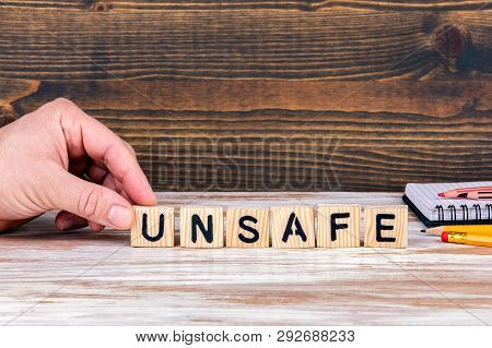 Unsafe. Wooden Letters On The Office Desk, Informative And Communication Background