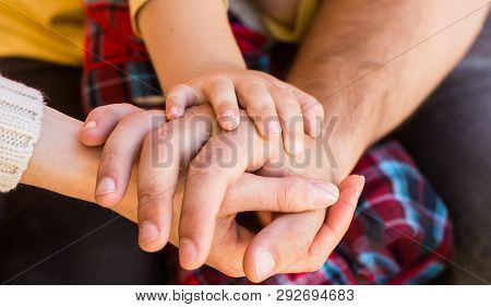 Child Hand Closeup Into Parents. Hands Of Father, Mother, Keep Hand Little Baby. Parents Hold The Ba