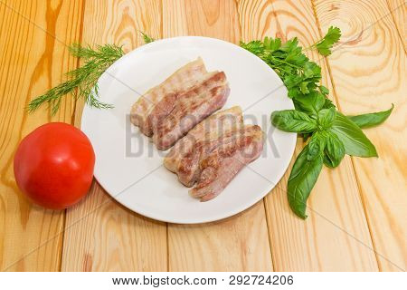 Two Slices Of The Grilled Streaky Bacon On The White Dish, Fresh Tomato And Different Greens On A Wo