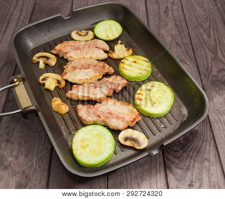Grilled Slices Of The Streaky Bacon, Vegetable Marrows And Mushrooms On The Grill Pan On The Old Woo