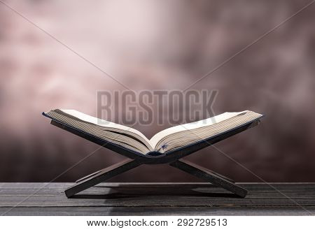 Quran Open In Wooden Placemat On Wooden Table Over Blurry Background