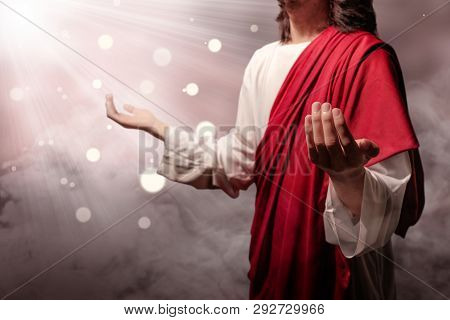 Jesus Christ Raised Hands And Praying To God With Ray Over Blurry Background