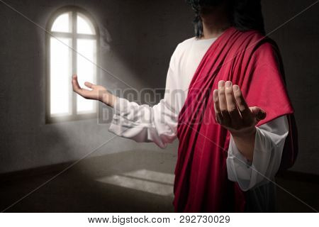 Jesus Christ Raised Hands With Open Palms And Praying To God Inside The Room With Light From Outside