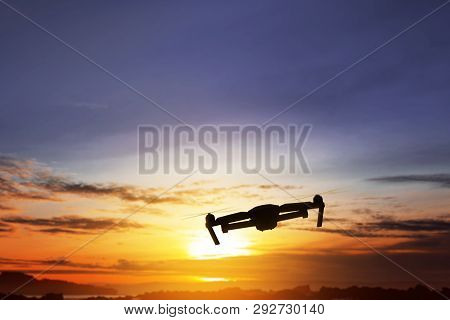 Silhouette Of Drone With Camera Flying Over Sunset View Background