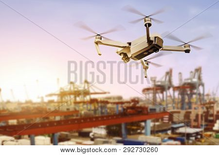 White Drone With Camera Flying Above The Dock With Sunset View Background