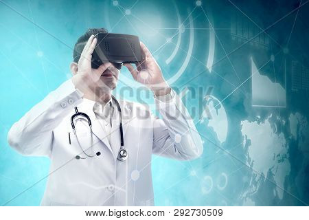 Asian Male Doctor In White Coat And Stethoscope Using Virtual Reality Device And Looking At Virtual