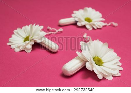 White Tampons And Flowers On A Pink Background.