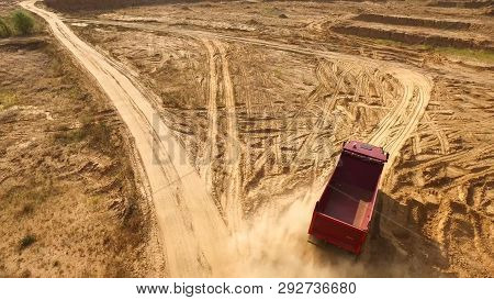 Truck Rides On Sand Quarry Road. Scene. Top View Of Dump Truck Driving On Yellow Dirt Road In Countr