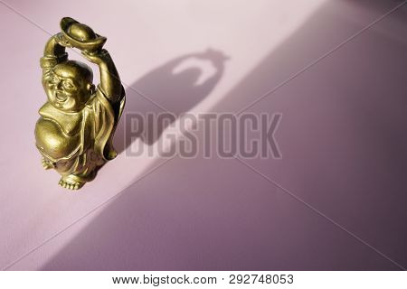 Budha Statue On Pink Background . Copy Space . Top View