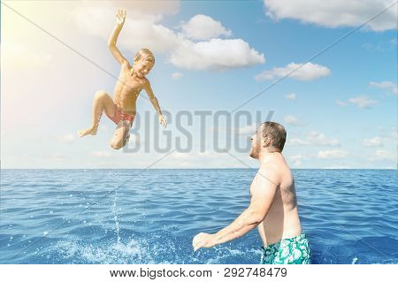 Adult Man And Kid Boy Having Fun Together At Sea Or Ocean. Dad With Son Playing On Beach,  Throwing