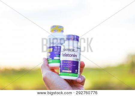 Bangkok,thailand - 1 Apr- 2019: Hand Lifting 10 Mg. Melatonin Pills On Sunset Background.melatonin T