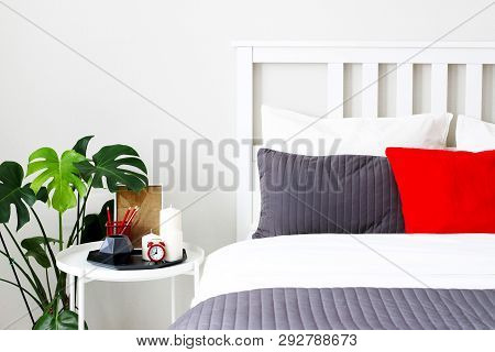 The Interior Of The Bedroom, Bed With Linens And Pillows. Monstera, Table, Alarm Clock Decor Element