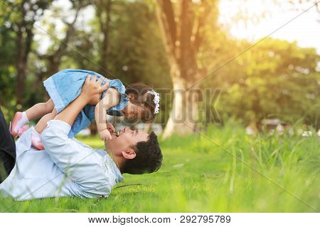 Father And Little Girl Play Lying On Grass, Low Angle