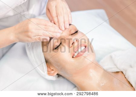 Cosmetology. The Hands Of A Cosmetologist Do A Facial Massage With A Mask. Smiling Girl On Spa Proce