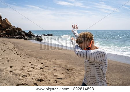 Adult Caucasion Woman Does A Dabbing Dance Move While On The Beach. Taken At Point Dume Malibu Calif