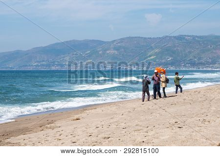 Malibu, California - March 26, 2019: Adult Tourists Take Selfies And Photos, Posing With Umbrella Pr